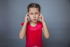 Girl covering her ears and eyes in a red dress on Royalty Free Stock Image