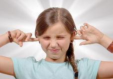 Girl covering her ears,to say stop making loud noise giving me Stock Photo
