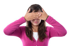 Girl covering her eyes. Girl dressed in pink covering her eyes on a white background royalty free stock image