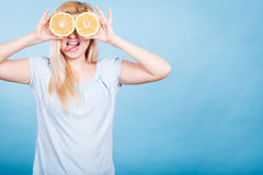 Girl covering her eyes with grapefruits Royalty Free Stock Photo