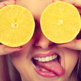 Girl covering her eyes with lemon citrus fruit Stock Photos