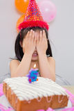 Girl covering her face at the birthday party Stock Photos