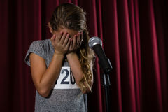 Girl covering her face with hand on stage Royalty Free Stock Image