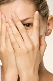 Girl covering her face with hands one eye exposed Stock Photos