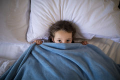Girl covering her face under the blanket while lying on bed. Portrait of girl covering her face under the blanket while lying on bed stock image