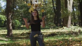 Girl is covering her face and waving a maple tree branch with yellow leaves in autumn park. Slow motion. 4k royalty free stock image