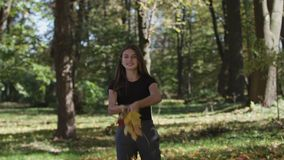 Girl is covering her face and waving a maple tree branch with yellow leaves in autumn park. Slow motion. 4k royalty free stock photos