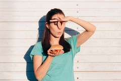 Woman Holding a Stinky and Disgusting Burger. Girl covering her nose because of Bad smelling dangerous food stock photography