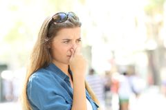 Girl covering her nose due to bad odour. In the street Royalty Free Stock Photography