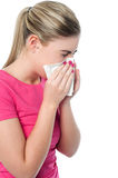 Girl covering her nose with handkerchief while sneezing Stock Photography