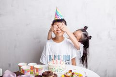 Girl covering his friend`s eyes with hands to make a surprise stock photo