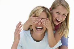 Girl (9-11) covering mother's eyes with hands Stock Photo