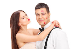Girl covering a young man in kisses Stock Photography
