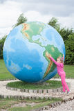 Girl covers the globe. Girl has a large globe Stock Images