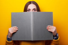 Girl covers her face with a book Stock Photos