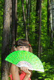 Girl covers her face with green fan Royalty Free Stock Photos