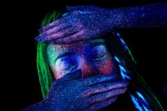 The girl covers her face with her hands. The girl aliens covers her face with her hands, ultraviolet make-up stock image