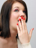 Girl Covers Her Mouth. A young girl puts her hand to her mouth Royalty Free Stock Images