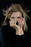 Girl covers her mouth with a black turtleneck Stock Photos