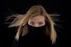 Girl covers her mouth with a black turtleneck Royalty Free Stock Photography