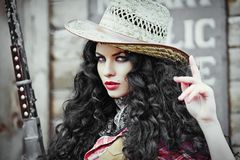 Girl in cowboy clothes and hat. Girl with black long and curly hair in cowboy clothes and hat. Young woman with a gun on a ranch royalty free stock photo