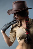 Girl cowboy. Cowboy woman with a glove in his hand on a gray background Royalty Free Stock Images
