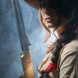 Girl cowboy. With a gun on a gray background Royalty Free Stock Photo