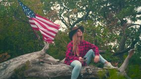 A girl in a cowboy hat in a plaid shirt sits on a log and drinks a tea. In the background, an American flag flutters.