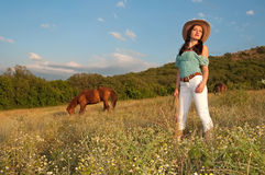 Girl Cowboy Standing In A Field With A Horse Royalty Free Stock Photography
