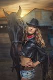 Girl cowboy standing near a horse. Stock Image