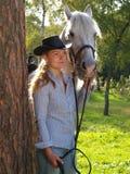 Girl-cowboy and white horse Royalty Free Stock Photos
