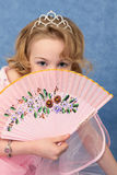 Girl coyly covered face with fan Stock Photography