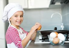 Girl cracking an egg Stock Photography