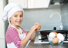 Girl cracking an egg Stock Photography