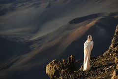 The girl at craters of Haleakala. Early morning, a smoke, wrapped up in white the girl in rising sun beams costs at edge of breakage against craters stock image