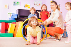 Girl crawl in plastic hoop, kindergarten group Royalty Free Stock Photos
