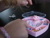 Girl crawls after beads in a pink box. Stock Images