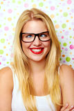 Girl with crazy smile. Portrait of blond haired girl with crazy smile and glasses, polka dot background Royalty Free Stock Image