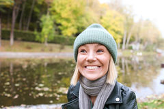 A girl with a crazy smile. On a lake shore in autumn Royalty Free Stock Images