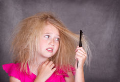 Girl with crazy tangled hair. Trying to comb it out royalty free stock images