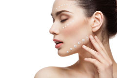 Girl with cream dots on face Stock Images
