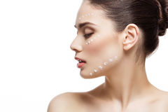 Girl with cream dots on face. Beautiful young woman with moisturizing cream dots on face. Isolated over white background. Copy space royalty free stock photo