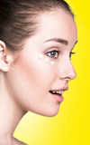 Girl with cream dots on face. On the yellow background stock image