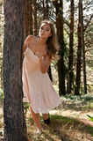 Girl in a cream dress in a forest Royalty Free Stock Photos