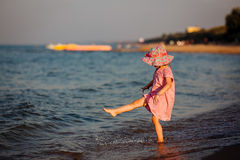 The girl creates splashes a foot at the sea Stock Photography