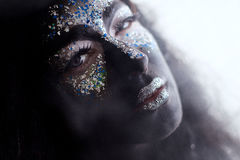 Girl with creative face art makeup smoking. Portrait of a girl with creative black face art makeup smoking stock image