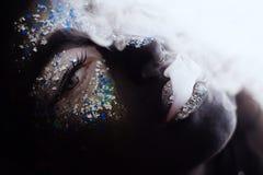 Girl with creative face art makeup smoking. Portrait of a girl with creative black face art makeup smoking royalty free stock photos