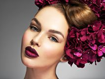 Girl with a creative hairstyle and blossoming flowers. In her hair. Young woman with a bouquet of purple flowers royalty free stock images