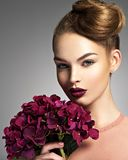 Girl with a creative hairstyle and blossoming flowers. Young woman with a bouquet of purple flowers stock image