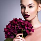 Girl with a creative hairstyle purple flowers. royalty free stock photography
